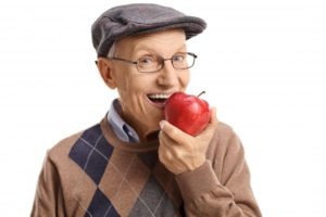 older man smiling holding apple