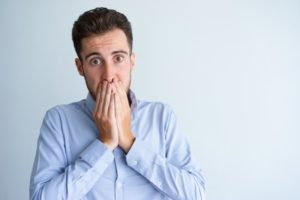 Embarrassed man covering mouth with bad breath needs his Naples dentist